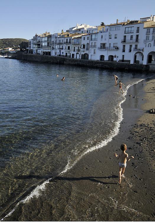 A boy runs along the beach in the small coastal village of Cadaques, Spain.