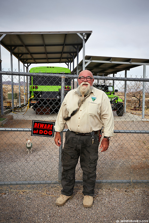 A friendly, large, bearded man stands smiling outside of his desert compound in New Mexico with a guard dog keeping a watchful eye.