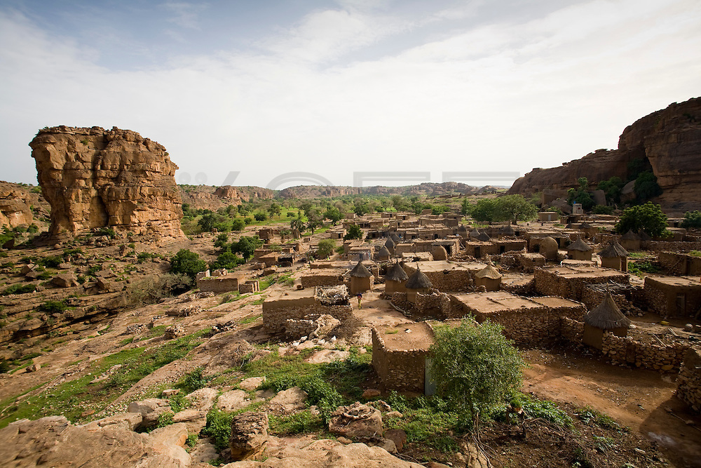 Panorama of Begnimato village. This village is very close to the border of the cliff and is surrounded by unusual rock formations. The Dogon Country is the most visited part of Mali with tourists visiting its tipical  villages that can be located on the cliff, on the sandy plain or in the rocky plateau