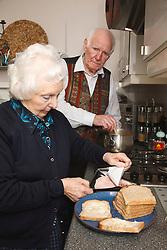 Elderly couple making sandwiches.