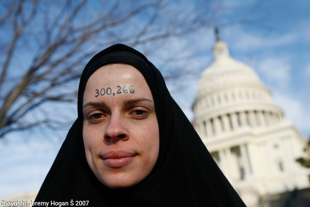 A rounded figure on how many Iraqi civilians have died since the U.S. invasion of Iraq in 2003 is painted on a woman's face. Over 100,000 anti-war protesters gathered on the Washington Mall and then marched on a route around the U.S. Capitol.