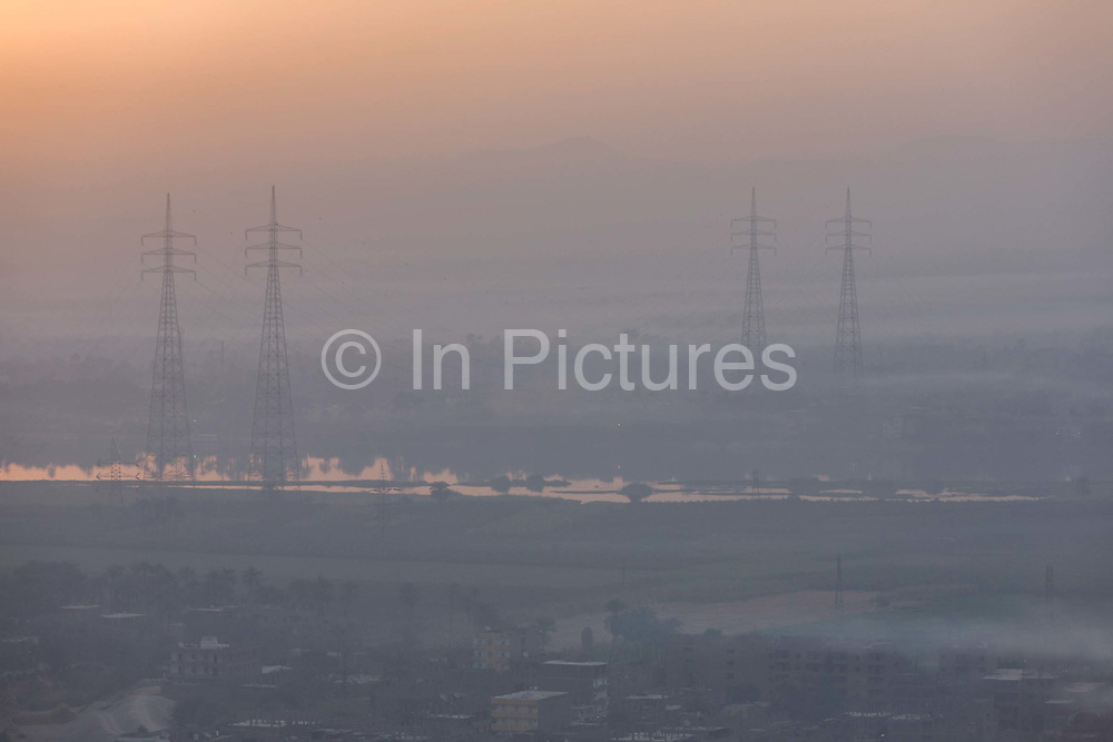 """Looking east from the West Bank bank of the river Nile, of a rising sun with electricity power pylons above the city of modern Luxor, Nile Valley, Egypt. The great African river can be seen reflecting riverbank vegetation. Egypt is classified as having a """"high power system size with 99% of the population having access to electricity although outages at all times of the day and night here on the West Bank of Luxor are regular and without warning."""