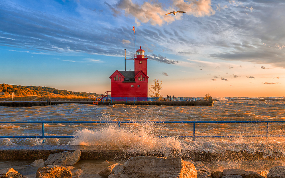 Waves splash on the shore as the sun sets on The Big red Lighthouse in Holland, Michigan