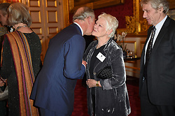 Dame Judi Dench, who along with Colin Firth earned her Oscar playing a member of the monarchy, greets the Prince of Wales during a reception for British Academy Awards winners at St James's Palace.