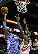 March 15, 2010; Houston, TX, USA; Denver Nuggets center Nene Hilario (31) lays a shot in over Houston Rockets forward Jordan Hill (27) in the second period at the Toyota Center.  The Rockets won 125-123. Mandatory Credit: Thomas Campbell-US PRESSWIRE