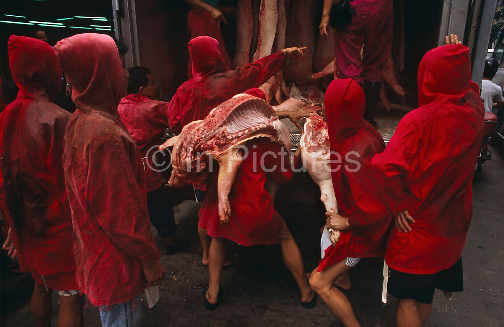 We are looking from behind a group of red uniformed meat market traders who are manhandling joints of pork from the back of a meat wagon at Macau's main meat market, on the Rua Sul do Mercado de Sao Domingos, just off the Avenida de Almeida Ribeiro, in Central Macau. The men have on hooded red tunics that hide the bloodstains of dead animal carcasses, a very practical choice of colour (color). One man has half a pig on his shoulders while another holds a leg in his left hand. The animal carcasses look heavy and they are both struggling under their weight. There is much more meat to be offloaded from the truck and the men queue up to take their turn and remove them for sale inside the market building. Besides historical Chinese and Portuguese world-heritage relics, Macau's biggest attraction is its gaming business. Its gambling revenue in 2006 weighed in at a massive £3.6bn - about £100m more than Las Vegas.  Administered by Portugal until 1999, it was the oldest European colony in China, dating back to the 16th century. The administrative power over Macau was transferred to the People's Republic of China (PRC) in 1999, 2 years after Hong Kong's own handover. Macau's name is derived from A-Ma-Gau or Place of A-Ma and this temple dedicated to the seafarers' goddess dates from the early 16th century.
