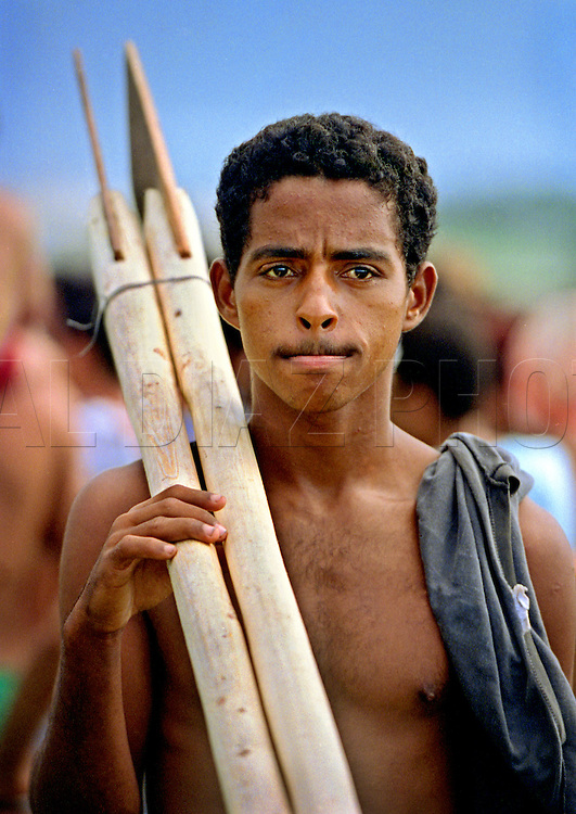 Pedro Hernandez, holding homemade oars anticipates his voyage on a homemade raft off the coast of Cojimar, Cuba. In 1994 Cuban balseros turned the tiny fishing village into a major point of embarkation for thousands seeking a better life. The mass exodus led to the 'Wet-foot, Dry-foot' United States Immigration Policy.