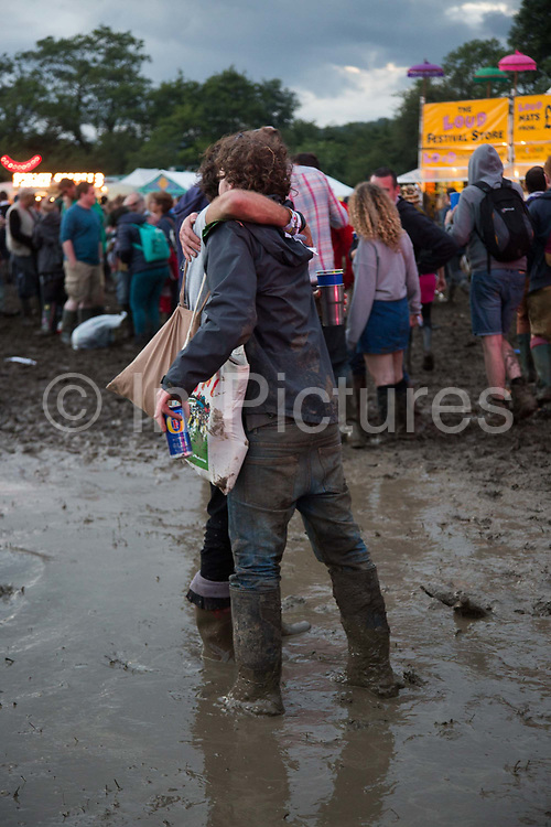 Party people hugging, stuck in mud at Glastonbury Festival 25th July 2016, Somerset, United Kingdom.  The Glastonbury Festival runs over 3 days and has 3000 acts, including music, art and performance and approx. 150.000 attend the anual event.