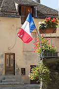 French flag sticking out of flowerpot in front of old cottage, Corps, France