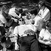 """Music Workshop student Barret DeYoung, of Connecticut, center, lounges on top of a picnic table while listening to friends play """"Here Comes the Sun,"""" on ukuleles along the shore of Green Lake at Interlochen Center for the Arts in Interlochen, Michigan."""