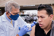 27 MARCH 2021 - DES MOINES, IOWA: Dr. YOGESH SHAH, Chief Medical Officer and Vice President of Medical Affairs at Broadlawns Medical Center, gives a COVID-19 vaccination to DANIEL SALDANA, a college student with COVID comorbidities, during a COVID-19 (Coronavirus) vaccination clinic at Corinthian Baptist Church in Des Moines, Saturday. The clinic was organized by Broadlawns Medical Center and the United Way and provided more than 1,100 shots to Des Moines area residents. The clinic was a part of an effort to reach communities of color in Iowa, who are vaccinated at rates below the state average.       PHOTO BY JACK KURTZ