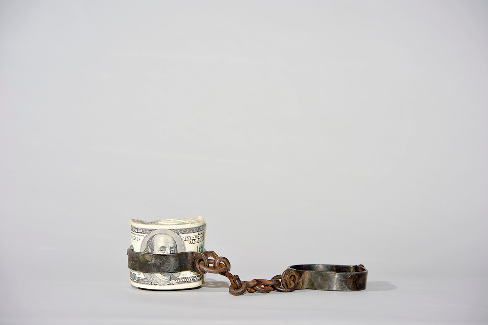 """December 06, 2014: A bundle of U.S. dollar bills rolled into antique slave shackles to illustrate a story titled """"How Slavery Made Capitalism.""""<br /> CREDIT: Matt Roth"""