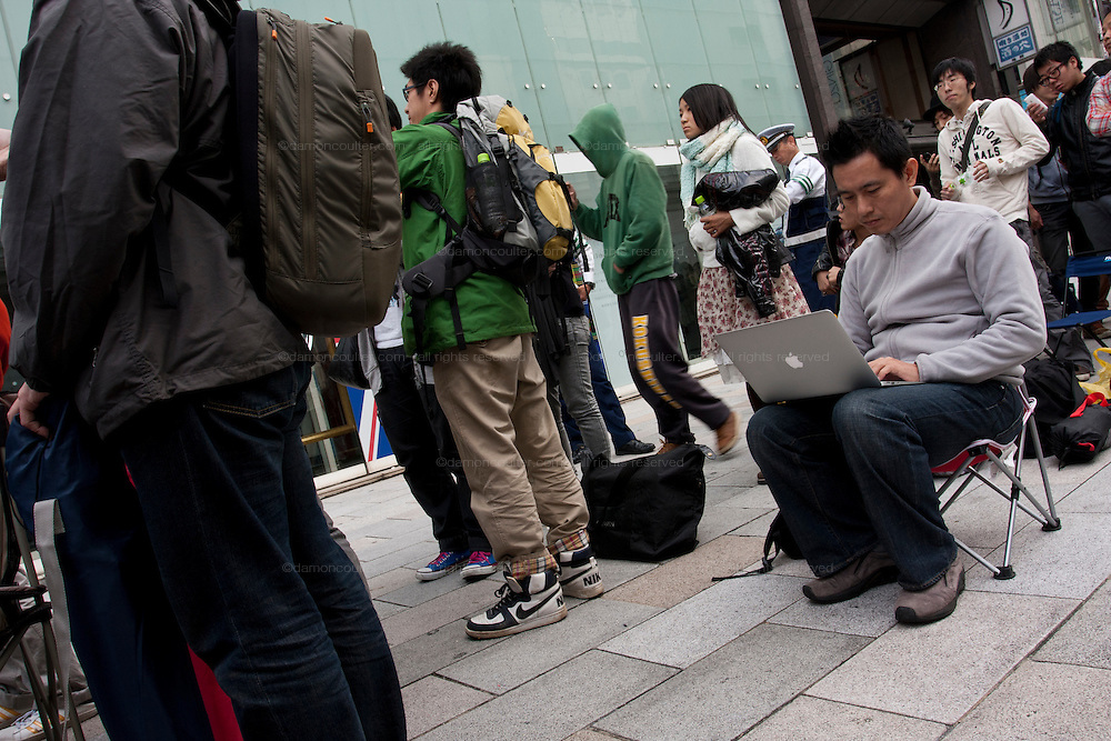 A man uses his Apple mac laptop computer as he waits in line with at the Apple store awaiting the official release of the iphone4S in Ginza, Tokyo, Japan. Friday October 14th 2011. The latest version of the popular iphone was released worldwide on October 14th. Japans flagship Apple store in Ginza was opened at 8am for the 800 people that had been waiting to be the first to purchase the new telephone.