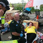 13 local activists locked themselves in specially made arm tubes to block the entrance to Quadrilla's drill site in New Preston Road, July 03 2017, Lancashire, United Kingdom. Medics attending Alana MMcCullogh are asked to attend another, hurt by police. The 13 activists included 3 councillors; Julie Brickles, Miranda Cox and Gina Dowding and Nick Danby, Martin Porter, Jeanette Porter,  Michelle Martin, Louise Robinson,<br /> Alana McCullough, Nick Sheldrick, Cath Robinson, Barbara Cookson, Dan Huxley-Blyth. The blockade is a repsonse to the emmidiate drilling for shale gas, fracking, by the fracking company Quadrilla. Lancashire voted against permitting fracking but was over ruled by the conservative central Government. All the activists have been active in the struggle against fracking for years but this is their first direct action of peacefull protesting. Fracking is a highly contested way of extracting gas, it is risky to extract and damaging to the environment and is banned in parts of Europe . Lancashire has in the past experienced earth quakes blamed on fracking.