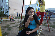 19 year old Isabella Baboi in the children's playground outside her home in Alexandria, where she lives with her mother and sister. She was expelled from France on 25th September by the police authorities for stealing chewing gum and face-cream. She declared herself as being homeless and returned to Romania with just the clothes she was wearing at the time of her arrest. She will return to Paris suburbs very soon, where her father and cousins are living. Alexandria, Romania..Roma Gypsies left India 1000 years ago. Often nomadic. A collection of tribes with their own languages and culture, pushed by the Ottoman empire towards Europe, used and sold as mercenaries, slaves, prostitutes. They endured 500 years of slavery until mid 19th century. A million were killed in the holocaust. Hundreds of thousands exiled and refugees from kosovo. Many Eastern Europe Roma come to the west seeking a better life. They are shunned, marginalized, excluded. Both indigenous and foriegn Roma, whether European citizens or not, lack the opportunities of others, living on the periphery, in the brunt of racism, often deported back to their countries of origin.