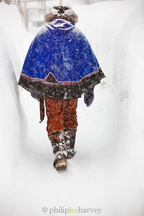 A Sami reindeer herder, in traditional dress, walks through the frozen snow at Kirkeness, northern Norway