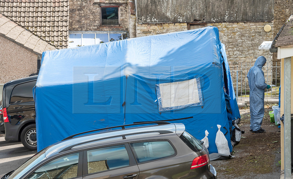 © Licensed to London News Pictures; 22/08/2020; Paulton, Bath and North East Somerset, UK. Police personnel with a tent search a garage behind house in Paulton after a man was arrested as part of an investigation by officers from Counter Terrorism Policing South East and South West. The man aged 33 was first arrested on Thursday (20/8) on suspicion of making or possessing an explosive substance in suspicious circumstances. He was then re-arrested on Friday (21/8) under section 41 of the Terrorism Act 2000 by detectives from Counter Terrorism Policing South East and South West. Officers carrying out this search are wearing protective suits due to the nature of this investigation and the Explosive Ordnance Disposal Team had been present at the property as a precaution. Police have said there is no wider threat to the public. Photo credit: Simon Chapman/LNP.