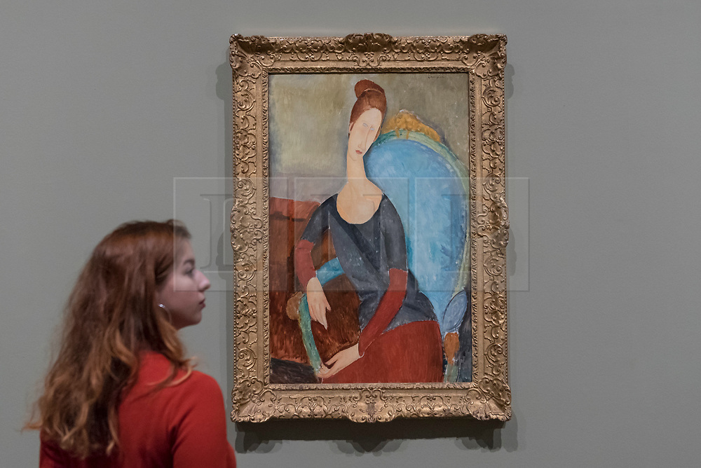 """© Licensed to London News Pictures. 21/11/2017. London, UK.  A staff member views """"Jeanne Hébuterne"""", 1918.  Preview of """"Modigliani"""", the most comprehensive exhibition of works by Amedeo Modigliani ever held in the UK.  On display are iconic portraits, sculptures and 12 nudes, the largest group ever shown in the UK.  The show runs 23 November to 2 April 2018.  Photo credit: Stephen Chung/LNP"""