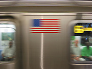New York City subway in motion speeding by a station