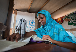 3 June 2019, Djohong, Cameroon: CAR refugee Adamou Madinatou works full time sewing dresses for women in the Borgop refugee camp and beyond. Together with five other refugees, she runs the Boutique Petit Piment ('The small peppers' boutique), a tailor's shop in the Borgop refugee camp grown out of a vocational training effort by the Lutheran World Federation. The Borgop refugee camp is located in the municipality of Djohong, in the Mbere subdivision of the Adamaoua regional state in Cameroon. Supported by the Lutheran World Federation since 2015, the camp currently holds 12,300 refugees from the Central African Republic.