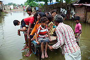 Children are playing on a cart, while crossing a small flooded road in Oriya Basti, Bhopal, Madhya Pradesh, India, a water-affected colony located near the former Union Carbide (now DOW Chemical) industrial complex.