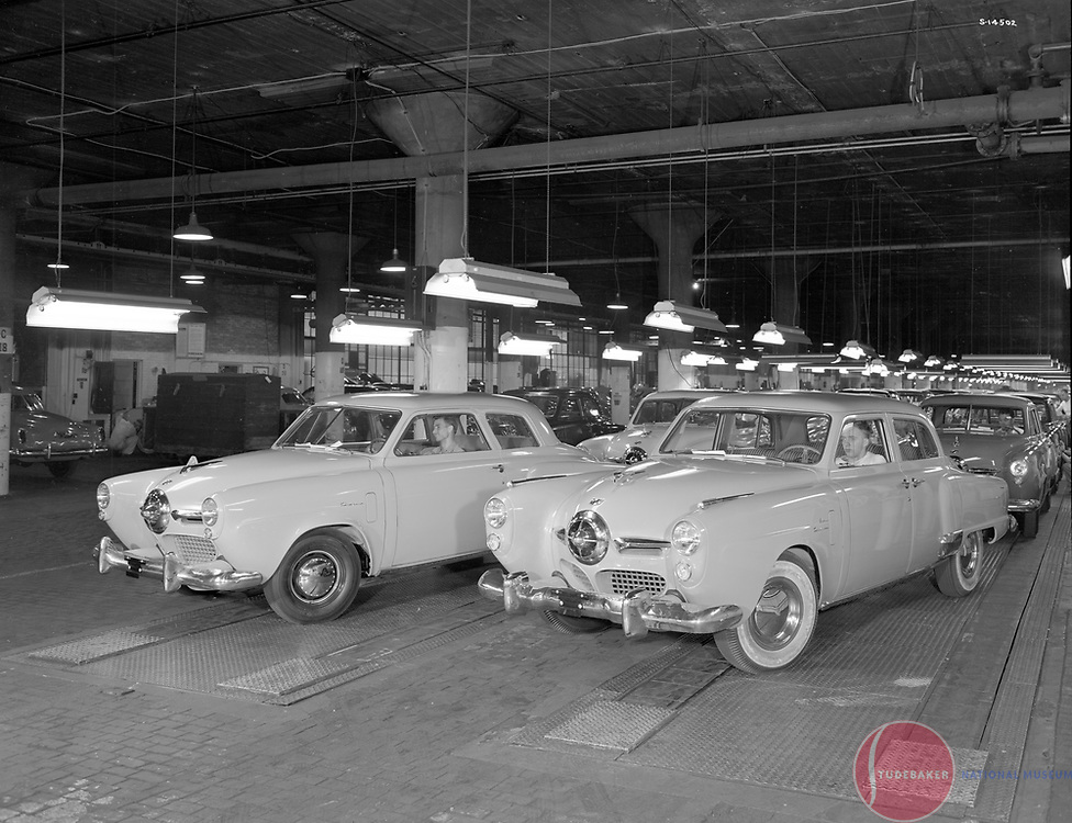 1950 Studebaker final assembly line.  A Champion (l) and a Land Cruiser (r) reach the end of the assembly line.