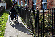 The wife of a prisoner leaves her Weymouth home in her wheelchair to visit her husband in HMP Portland. Dorset., United Kingdom.