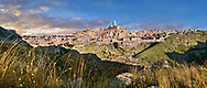 """Panoramic long view across """"la Gravina"""" ravine to the Sassi of Matera at sunrise, Basilicata, Italy. A UNESCO World Heritage site.<br /> <br /> The area of Matera has been occupied since the Palaeolithic (10th millennium BC) making it one of the oldest continually inhabited settlements in the world. <br /> The town of Matera was founded by the Roman Lucius Caecilius Metellus in 251 BC and remained a Roman town until  was conquered by the Lombards In AD 664 becoming part of the Duchy of Benevento.  Matera was subject to the power struggles of southern Italy coming under the rule of the Byzantine Roman, the Germans and finally Matera was ruled by the Normans from 1043 until the Aragonese took possession in the 15th century. <br /> <br /> At the ancient heart of Matera are cave dwellings known as Sassi. As the fortunes of Matera failed the sassy became slum dwelling and the appalling living conditions became be the disgrace of Italy. From the 1970's families were forcibly removed from the Sassi and rehoused in the new town of Matera. Today tourism has regenerated Matera and the sassi have been modernised and are lived in again making them probably the longest inhabited houses in the world dating back 9000 years."""