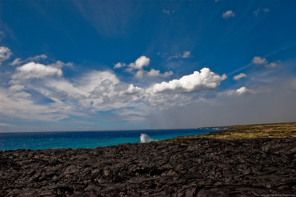 A wave crashes against a wall of young earth; another beautiful day in Hawaii's Volcanoes National park