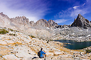 Hiker under Isosceles Peak and the Palisades in Dusy Basin, Kings Canyon National Park, California USA