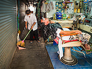 """06 FEBRUARY 2017 - BANGKOK, THAILAND:  A barber sweeps up her shop after giving a customer a haircut in what used to be known as Kalabok Market under the Phra Khanong Bridge in the Phra Khanong district of Bangkok. Kalabok is the Thai word for hairdresser and the market was called Kalabok because there were many barbershops and hairdressers under the bridge. In 1985, the city changed the name of the market to """"Singha Market."""" There are still about 10 small men's barbershops, most with just one barber, and four women's salons, most with one hairdresser,  under the bridge.     PHOTO BY JACK KURTZ"""