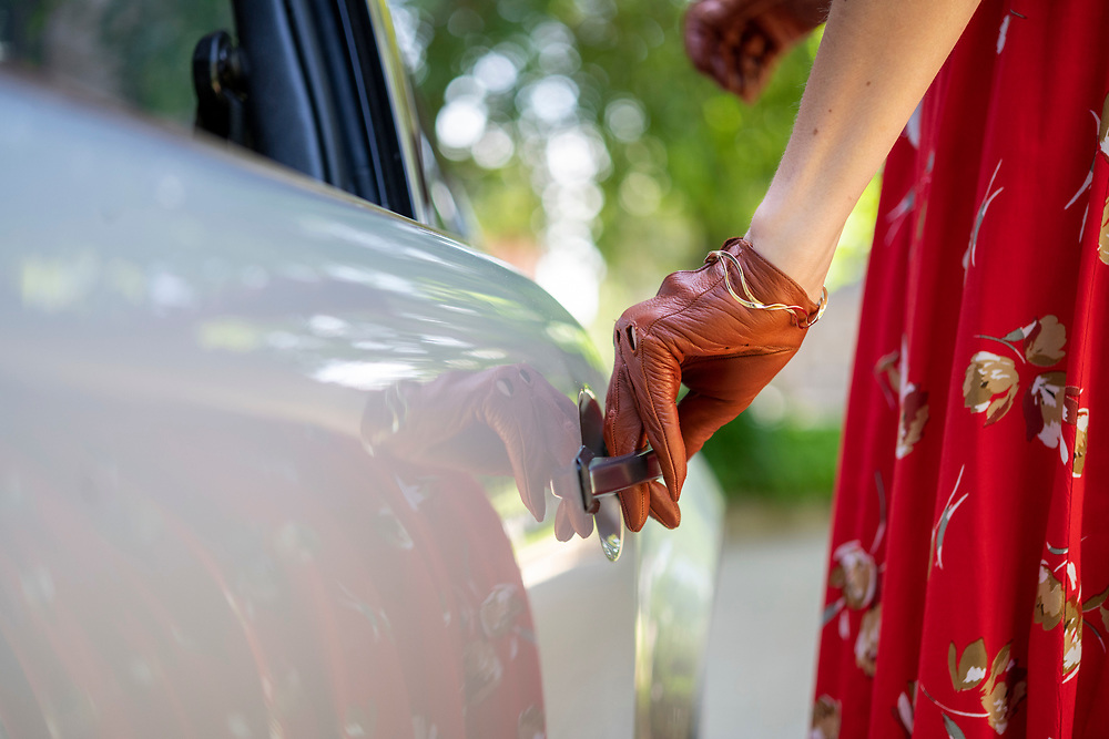 """Lancaster, Pennsylvania - June 09, 2019: Caroline Ecklin wears driving gloves given to her by her mother.<br /> <br /> Caroline Ecklin with """"Sally"""" her 1980 Porsche 911 outside the Stevens School apartments in Lancaster, Pa., Sunday June 9, 2019. The 27-year-old car restoration garage manager names her cars, and this one is after the Disney Pixar Porsche character in the movie """"Cars.""""<br /> <br /> <br /> CREDIT: Matt Roth for The Wall Street Journal"""