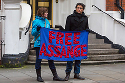 Two Assange supporters with their banner outside the entrance to the Ecuador Embassy. A small group of Julian Assange supporters gather outside the embassy of Ecuador where the Wikileaks founder has been holed up for nearly six years. His arrest warrant for breaching bail conditions has been upheld by Westminster Magistrates Court. London, February 13 2018.
