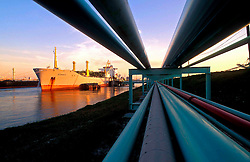Oil tanker and pipelines in Port of Houston at dusk.
