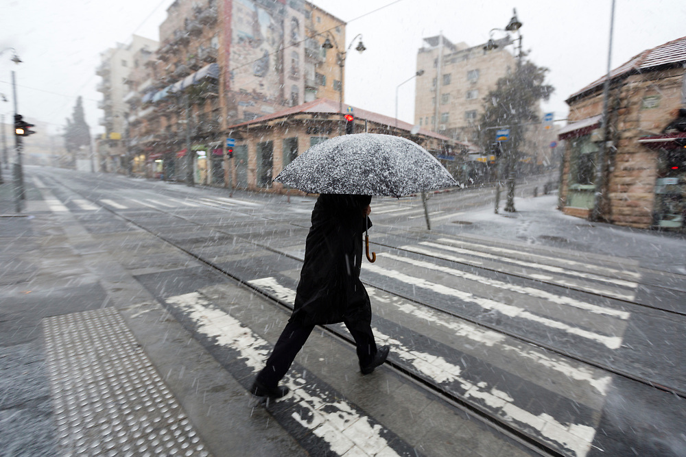 A man protects himself with an umbrella while crossing Jaffa Street, as snow falls during a winter storm in Jerusalem, Israel, on January 7, 2015.