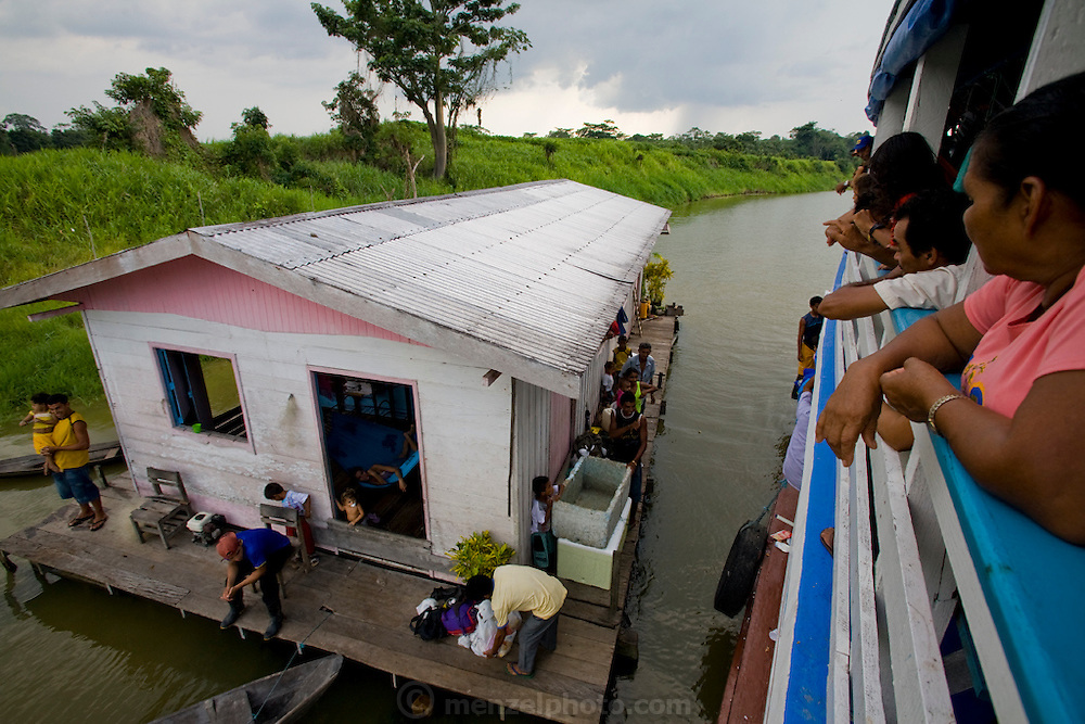 Families go about their daily business on a houseboat on the Solimoes River in Brazil after a passenger disembarks from a riverboat that stopped at their floating house.  Riverboats ply the network of rivers that drain the vast Amazon basin which has very few roads.