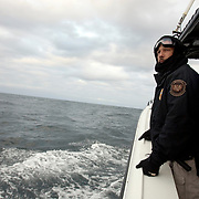 """Keley Hill, Director of Marine Interdiction unit of  Customs and Border Protection, .San Diego Air & Marine Branch, patrols the waters near the US/Mexico border for undocumented immigrants in the early morning hours. The unit is also on patrol for gun smugglers hauling firearms into Mexico which is helping to fuel the Narco wars raging in Mexico. For more images, search for """"immigration by air and sea"""". Please contact Todd Bigelow directly with your licensing requests."""