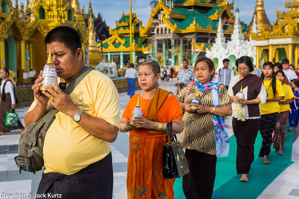 07 JUNE 2014 - YANGON, YANGON REGION, MYANMAR: People participate in a small private procession during a merit making ceremony for their company at Shwedagon Pagoda in Yangon. Shwedagon Pagoda is officially called Shwedagon Zedi Daw and is also known as the Great Dagon Pagoda and the Golden Pagoda. It's a 99 metres (325ft) gilded pagoda and stupa located in Yangon. It is the most sacred Buddhist pagoda in Myanmar with relics of the past four Buddhas enshrined within: the staff of Kakusandha, the water filter of Koṇāgamana, a piece of the robe of Kassapa and eight strands of hair from Gautama, the historical Buddha.   PHOTO BY JACK KURTZ