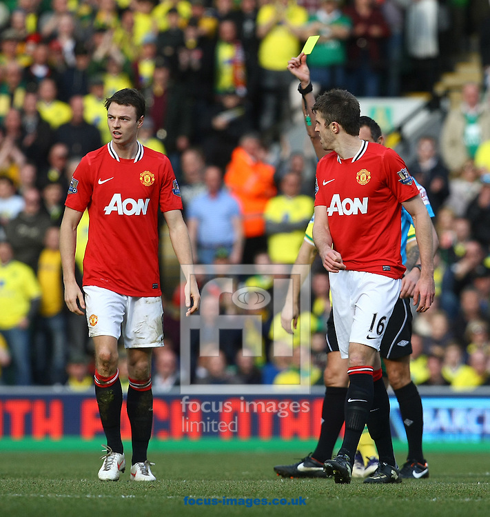 Picture by Paul Chesterton/Focus Images Ltd.  07904 640267.26/02/12.Jonny Evans of Man Utd gets a yellow card from Referee Andre Marriner during the Barclays Premier League match at Carrow Road Stadium, Norwich.