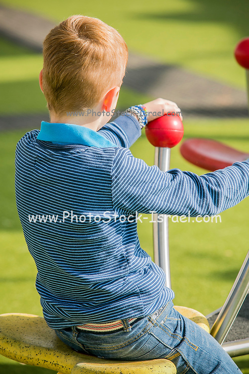 Young red haired boy plays alone in a park