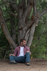 Rugged man sitting under a tree in New Mexico