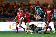 Gareth Davies of the Scarlets breaks away from the tackle of Lloyd Williams (on ground) and Josh Turnbull of Cardiff Blues (jumping).  Guinness Pro14 rugby match, Scarlets v Cardiff Blues  at the Parc y Scarlets in Llanelli, West Wales on Saturday 28th October 2017.<br /> pic by  Andrew Orchard, Andrew Orchard sports photography.