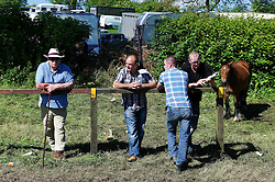 © Licensed to London News Pictures. <br /> 06/06/2014. <br /> <br /> Appleby, Cumbria, England<br /> <br /> Men stand and watch the horses as they are paraded as gypsies and travellers gather during the annual horse fair on 6 June, 2014 in Appleby, Cumbria. The event remains one of the largest and oldest events in Europe and gives the opportunity for travelling communities to meet friends, celebrate their music, folklore and to buy and sell horses.<br /> <br /> The event has existed under the protection of a charter granted by King James II in 1685 and it remains the most important event in the gypsy and traveller calendar.<br /> <br /> Photo credit : Ian Forsyth/LNP