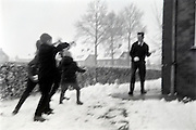 Blurred motion of snow throwing children and father 1960s Holland