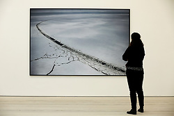 """© Licensed to London News Pictures. 14/03/2019. London, UK. A woman views a photograph of Cape Kamenny, Yamal Peninsula, Russia May 2018. <br /> Carmignac Photojournalism award - """"Arctic - New Frontier"""" exhibition by Yuri Kozyrev and Nadir Vab Lohuizen on show at Saatchi Gallery. Yuri Kozyrev and Kadir van Lohuizen (NOOR) were awarded the 9th edition of the Carmignac Photojournalism Award dedicated to the Arctic. The endowment allowed them to carry out their pioneer double polar expedition 'Arctic: New Frontier'. <br /> The exhibition runs from 15 March, it will run until 5 May 2019 at Saatchi Gallery. Photo credit: Dinendra Haria/LNP"""