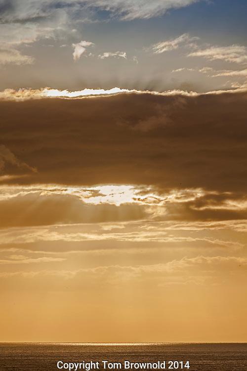 sun beaming through the cloud cover at sea
