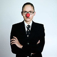 studio shot portrait of a beautiful one young business woman in a costume suit with a clown nose on isolated grey background