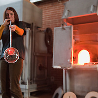 VENICE, ITALY - DECEMBER 18:  Elena Rosso a glass  artist in Murano blows a Christmas bauble next to a glass furnace on December 18, 2010 in Venice, Italy. There are only few female glass artists is Italy and they face continuous challanges in a traditionally male dominated field.