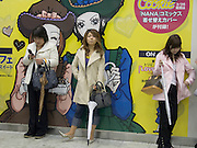 young girls waiting after work for there friends in front of a large comic magazine billboard at the entrance to the train