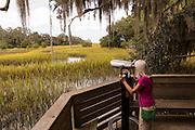 Elderly woman uses a binocular viewer on salt marsh boardwalk at Honey Horn Plantation on Hilton Head Island, SC